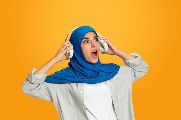 노란 벽에 고립 된 젊은 이슬람 여자의 초상화
