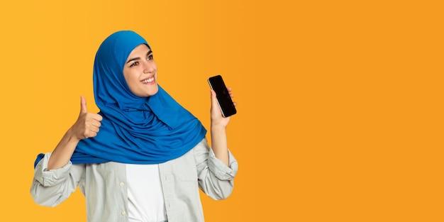 黄色で隔離の若いイスラム教徒の女性の肖像画