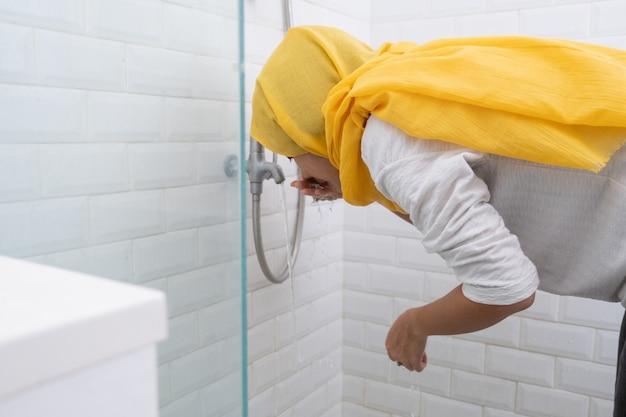 젊은 무슬림 여성의 초상은 집에서기도하기 전에 재계 (wudhu)를 수행합니다.