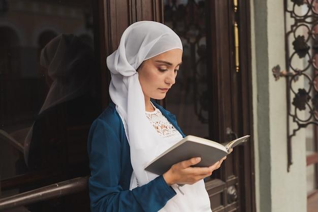 屋外で本を読んでヒジャーブを身に着けている若いイスラム教徒の女性の肖像画