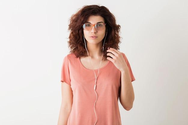 イヤホンで音楽を聴く、白いスタジオの背景に分離された眼鏡をかけているポーズのピンクのシャツで巻き毛のヘアスタイルを持つ若い自然な流行に敏感なきれいな女性の肖像画