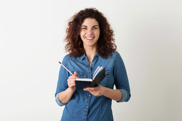 Портрет молодой натуральной хипстера, улыбающейся красивой женщины с вьющейся прической в джинсовой рубашке, позирующей с блокнотом и ручкой на белом фоне студии, обучение студента