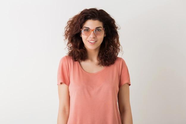 白いスタジオの背景に分離された眼鏡をかけてポーズをとってピンクのシャツで巻き毛のヘアスタイルを持つ若い自然な笑みを浮かべて流行に敏感なきれいな女性の肖像画