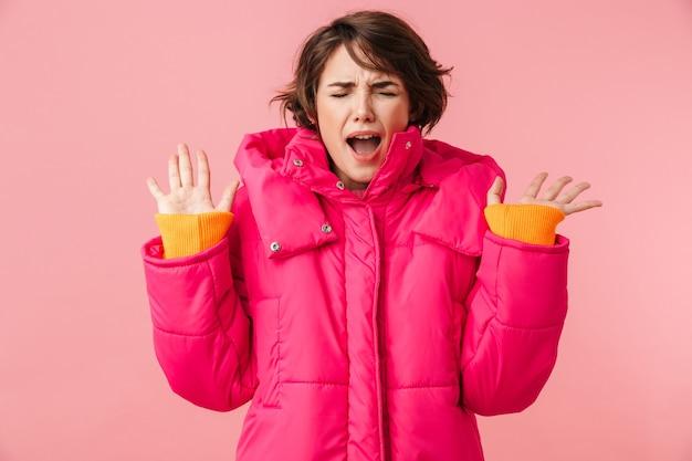 분홍색에 고립된 손으로 비명을 지르는 따뜻한 코트를 입은 젊은 신경질적인 여성의 초상화