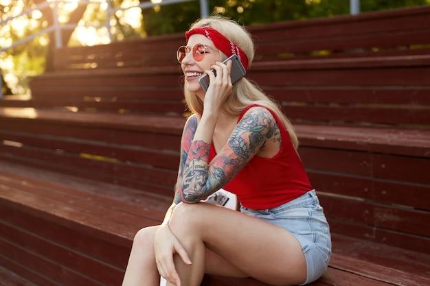 入れ墨の腕を持つ若い素敵なブロンドの女性の肖像画、耳にスマートフォンを持って、彼の友人と話しています。赤いtシャツの耳、デニムのショートパンツ、頭にバンダナのニット、赤いメガネ。