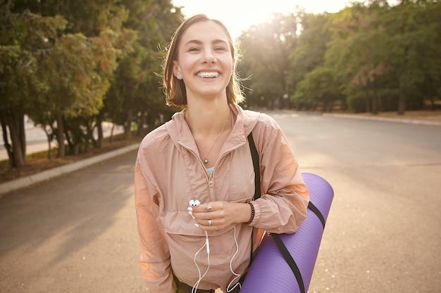 公園でヨガの後に歩いて、ヘッドフォンで音楽を聴いて、気分が良くて笑顔で、涼しい日を楽しんでいる若い素敵な女の子の肖像画。
