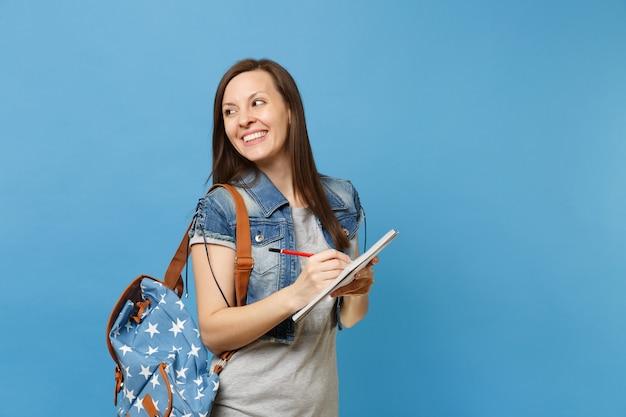 파란색 배경에 격리된 노트북에 메모를 작성하는 쪽을 바라보며 배낭을 메고 데님 옷을 입은 젊고 즐거운 여학생의 초상화. 고등학교 대학 대학 개념의 교육입니다.