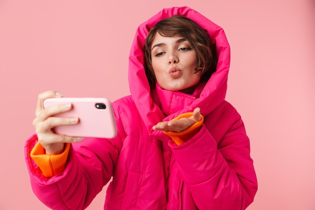 Портрет молодой красивой женщины в теплом пальто, делающей селфи-фото и отправляющей воздушный поцелуй, изолированный на розовом