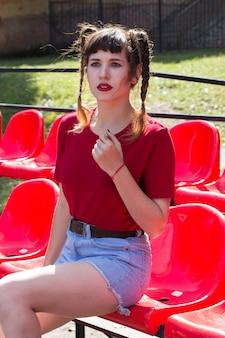 赤いtシャツを着て野球場の座席に若い普通の美しいtennager女の子モデルの肖像画 Premium写真