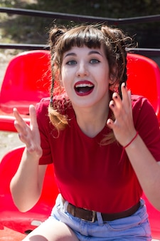 赤いtシャツを着て野球場の座席に若い普通の美しいtennager女の子モデルの肖像画