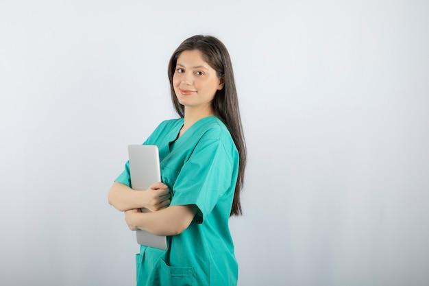 Портрет молодой медсестры, держащей компьтер-книжку на белизне.