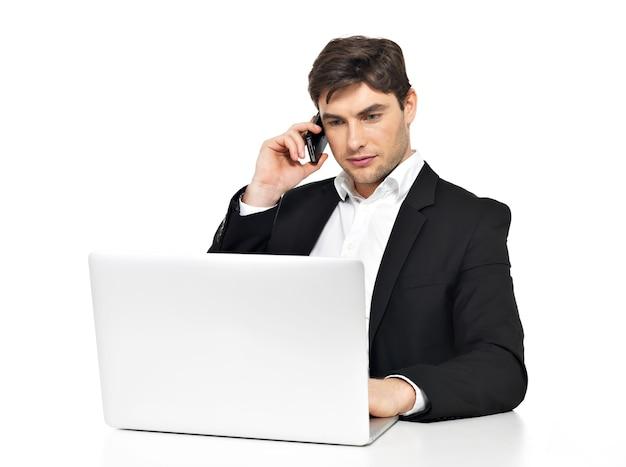ノートパソコンを持つ若いサラリーマンの肖像画は、白で隔離のテーブルに座っている携帯電話で話します。