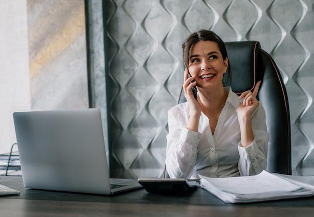 사무실에서 행복 한 얼굴 작업 과정으로 웃 고 휴대 전화에 얘기하는 사무실 책상에 앉아 젊은 회사원 여자의 초상화