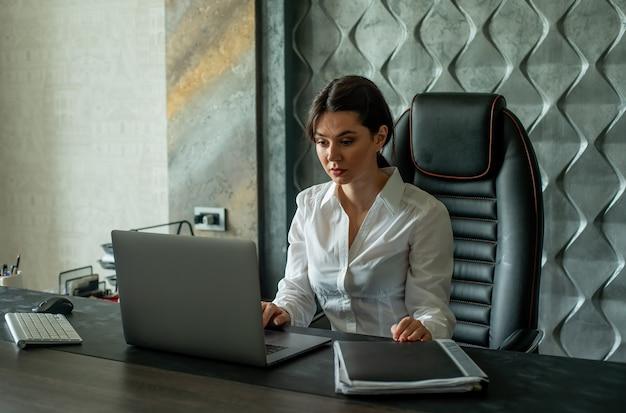 사무실에서 일하는 얼굴에 심각하고 자신감있는 표정으로 바쁜 찾고 랩톱 컴퓨터를 사용하여 사무실 책상에 앉아 젊은 회사원 여자의 초상화