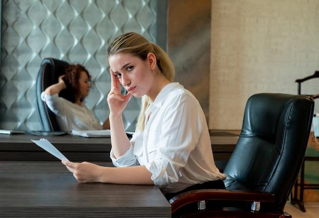 退屈で過労のオフィスに座っている文書を探してオフィスの机に座っている若いサラリーマン女性の肖像画