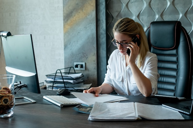 Портрет молодой женщины офисного работника, сидящей за офисным столом с документами, разговаривает по мобильному телефону с уверенным и серьезным выражением лица, работая в офисе