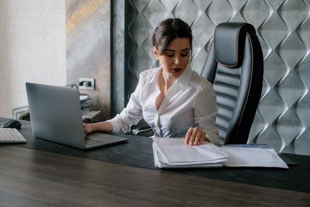 Портрет молодой женщины офисного работника, сидящей за офисным столом с документами, с помощью портативного компьютера, выглядящей уверенно и занятой работой в офисе