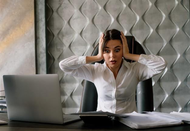 ノートパソコンの電卓とそれらを見てドキュメントのオフィスの机に座っている若いサラリーマン女性の肖像画に衝撃を与えた本社のコンセプトに触れる