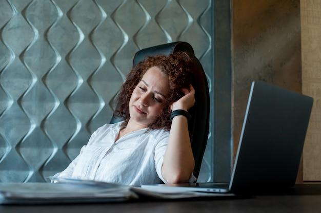 사무실에서 일하는 얼굴에 잠겨있는 표정으로 제쳐두고 찾고 노트북 컴퓨터와 사무실 책상에 앉아 젊은 회사원 여자의 초상화