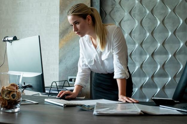 オフィスで働く顔に自信を持って、深刻な表情でコンピューターを使用してドキュメントをオフィスの机に立っている若いサラリーマン女性の肖像画