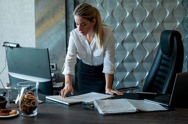 사무실에서 일하는 얼굴에 자신감과 심각한 표정으로 컴퓨터를 사용하는 문서와 함께 사무실 책상에 서있는 젊은 회사원 여자의 초상화