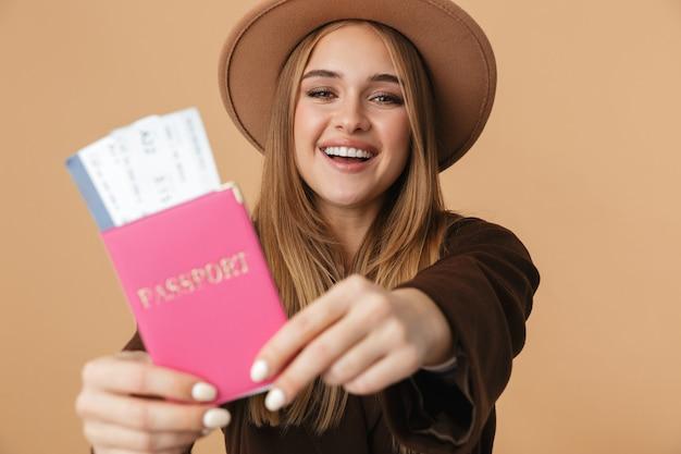 Портрет молодой оптимистичной девушки в шляпе, держащей паспорт и проездные билеты, изолированные на бежевом