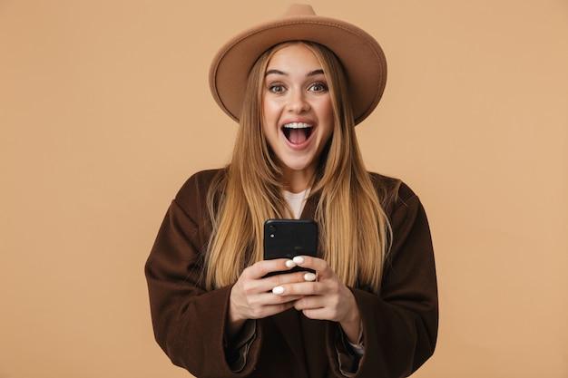 Портрет молодой оптимистичной девушки в шляпе, смеющейся и держащей мобильный телефон, изолированной на бежевом