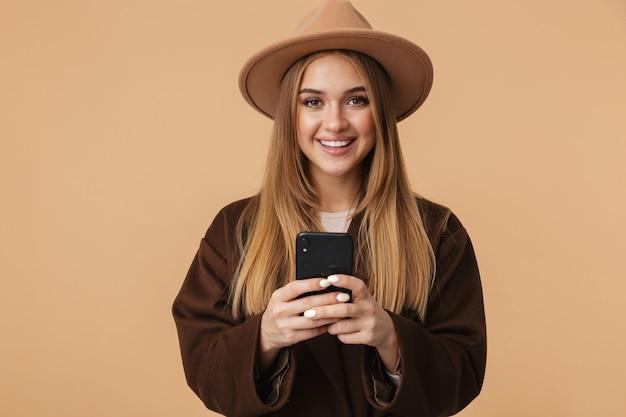 Портрет молодой оптимистичной девушки в шляпе, улыбающейся и держащей мобильный телефон, изолированной на бежевом