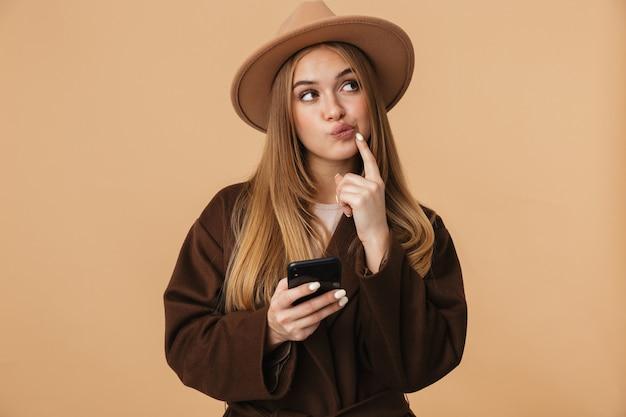 Портрет молодой оптимистичной девушки в шляпе, думающей и держащей мобильный телефон, изолированной на бежевом
