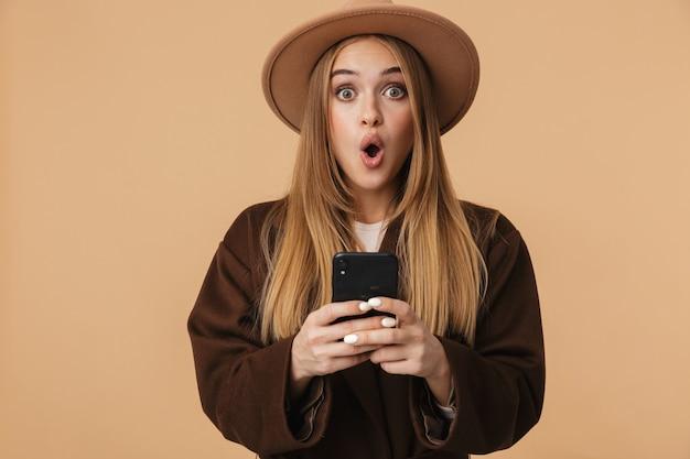 Портрет молодой оптимистичной девушки в шляпе, гадающей и держащей мобильный телефон, изолированной на бежевом