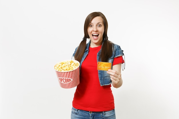 흰색 배경에 격리된 팝콘 양동이와 신용카드를 들고 영화 영화를 보는 캐주얼한 옷을 입은 젊은 매력적인 브루네트 여성의 초상화. 영화 개념의 감정.