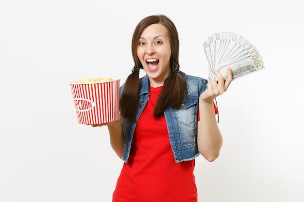 캐주얼 옷을 입고 영화 영화를 보고, 팝콘 양동이와 달러 묶음, 흰색 배경에 격리된 현금 돈을 들고 기뻐하는 젊은 예쁜 여성의 초상화. 영화 개념의 감정.