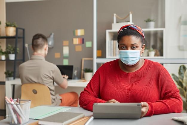 Портрет молодой женщины с избыточным весом в защитной маске, смотрящей вперед, сидя на рабочем месте и работая на планшетном пк в офисе