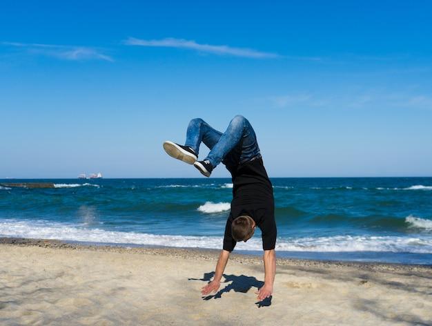 ビーチでフリップまたは宙返りをしている若いパルクールの男の肖像画。フリップの凍結した瞬間。