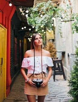 Портрет молодой страстной туристической женщины с ретро камерой в руках, позируя на городской старой архитектуре. открывайте новые места