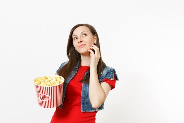 캐주얼 옷을 입고 영화 영화를 보고, 팝콘 양동이를 들고, 올려다보고, 흰색 배경에 격리된 턱 근처에 손을 잡고 있는 수심에 찬 젊은 아름다운 여성의 초상화. 영화 개념의 감정.