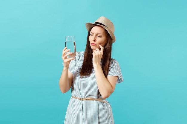 파란 드레스를 입고 모자를 쓰고 파란 배경에 격리된 유리에서 맑고 깨끗한 물을 마시는 수심에 잠긴 젊은 여성의 초상화. 건강한 생활 방식, 사람들은 진실한 감정 개념입니다. 공간을 복사합니다.