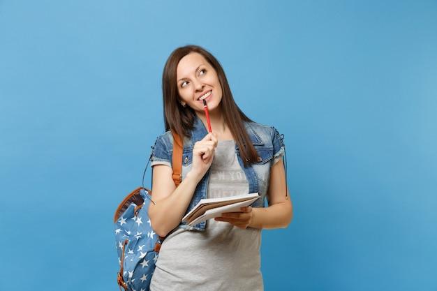파란색 배경에 격리된 노트북, 연필을 들고 꿈꾸는 생각을 하고 배낭을 메고 데님 옷을 입은 젊은 수심에 찬 여학생의 초상화. 고등학교 대학 대학에서 교육.