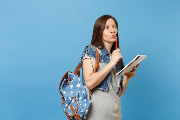 파란색 배경에 격리된 노트북 연필을 들고 시험을 생각하는 배낭을 메고 데님 옷을 입은 수심에 찬 젊은 여학생의 초상화. 고등학교 대학 대학에서 교육.