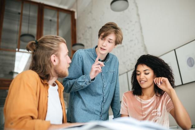 オフィスで何かを議論している若者の肖像画。ブロンドの髪の2人の男の子と暗い巻き毛の女の子が教室で一緒に勉強しています