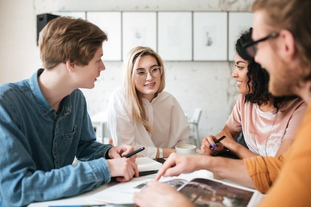 Портрет молодых людей, сидящих в офисе и счастливо смотрящих друг на друга во время обсуждения чего-то