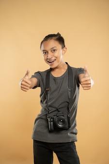 Портрет улыбающегося молодого фотографа, держащего свою профессиональную камеру Premium Фотографии