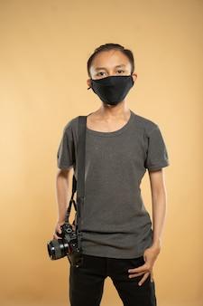 Портрет улыбающегося молодого фотографа, держащего свою профессиональную камеру