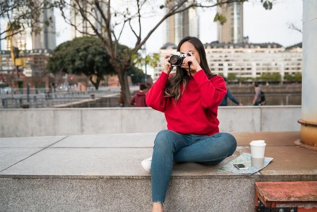 야외에서 전문 디지털 카메라를 사용하는 젊은 사진 작가 여자의 초상화. 사진 컨셉
