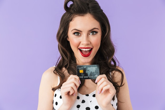 紫色の壁に分離されたプラスチック製のクレジットカードを保持しながら笑っているヴィンテージ水玉ドレスの若いピンナップ女性の肖像画