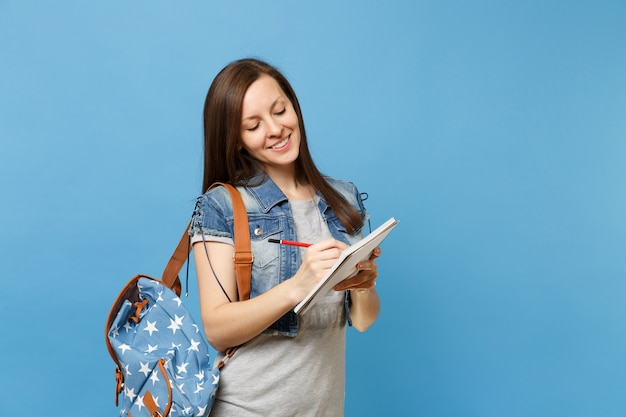 회색 티셔츠를 입은 젊고 귀여운 여학생의 초상화, 파란색 배경에 격리된 노트북에 배낭이 달린 데님 옷. 고등학교 대학 대학 개념의 교육입니다.