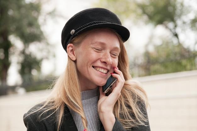 좋은 전화 통화를하고 진심으로 웃고 검은 모자와 회색 따뜻한 우아한 옷을 입은 야외 포즈를 취하는 동안 눈을 감고 눈을 감은 젊은 즐거운 찾고 금발 아가씨의 초상화