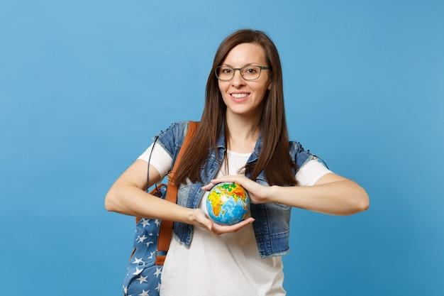 파란색 배경에 격리된 세계 글로브를 들고 배낭을 메고 안경을 쓴 젊은 유쾌한 웃는 여자 학생의 초상화. 대학에서 교육입니다. 행성을 저장합니다. 생태 환경 보호 개념입니다.