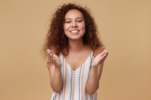 베이지 색에 서있는 성실한 미소로 기꺼이 보면서 그녀의 손바닥을 유지하는 젊은 기쁘게 사랑스러운 긴 머리 곱슬 갈색 머리 아가씨의 초상화