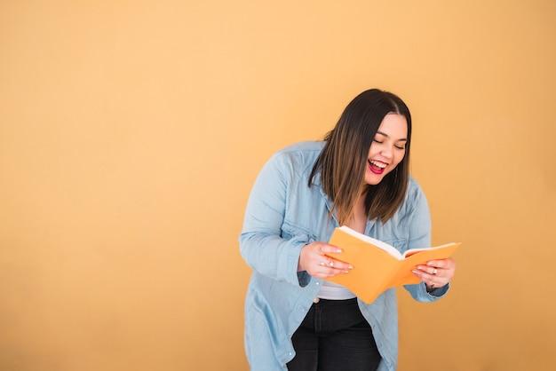 자유 시간을 즐기고 노란색 배경에 서있는 동안 책을 읽는 젊은 더하기 크기 여자의 초상화. 라이프 스타일 개념.